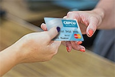 Close up of woman handing her credit card to merchant.