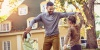 Man dancing with two children in the yard of a home.